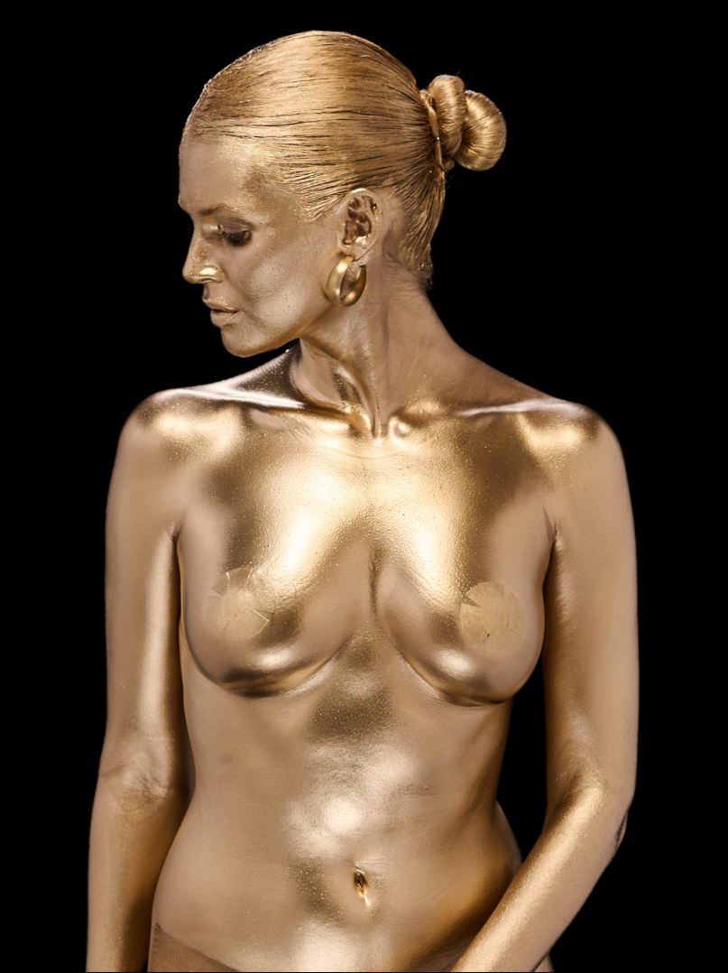 Photo of woman covered with gold paint on black background