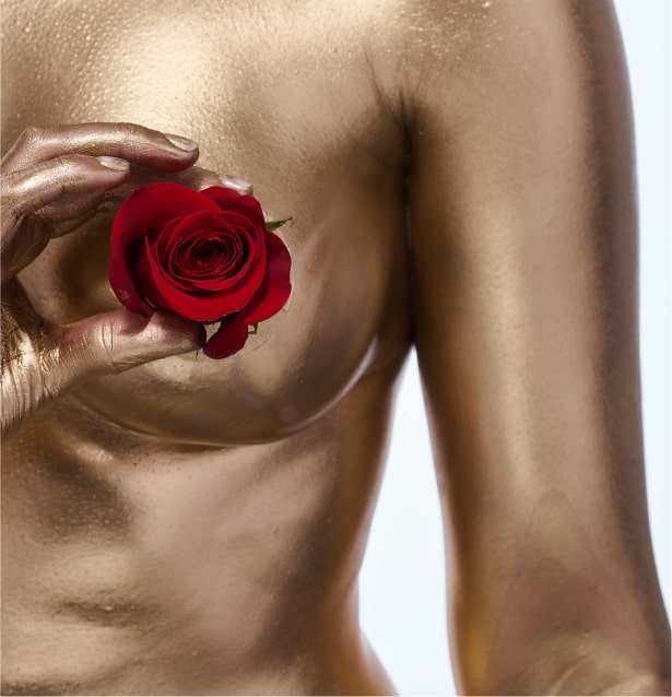 Photo of woman covered with gold paint holding rose in her hand