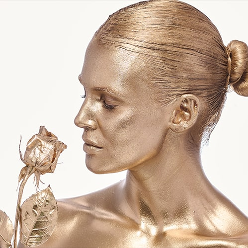 woman covered with gold paint holding rose in her hands